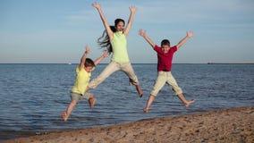 Grupo de tres niños que saltan en la playa en el centro turístico de Egipto, m lento almacen de video