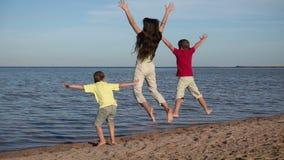Grupo de tres niños que saltan en la playa en el centro turístico de Egipto, m lento almacen de metraje de vídeo