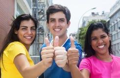 Grupo de tres personas jovenes en las camisas coloridas que muestran los pulgares Foto de archivo