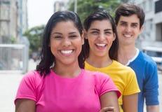 Grupo de tres personas jovenes en las camisas coloridas que se colocan en línea Fotos de archivo