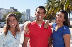 Grupo de tres personas latinas felices en la ciudad Fotos de archivo