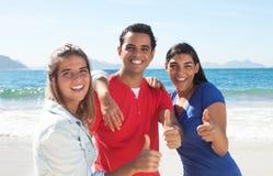 Grupo de tres personas latinas felices en la playa Imagenes de archivo
