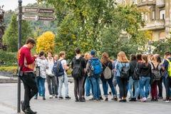 Grupo de turistas adolescentes que se colocan y que esperan en un poste indicador de la calle alrededor para ir en un viaje en Bu Fotos de archivo