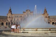 Grupo de turistas de las muchachas en la fuente del cuadrado de España de Sevilla imagen de archivo