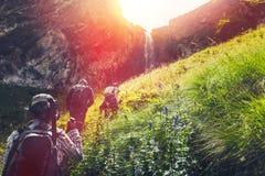 Grupo de turistas de los caminantes que caminan cuesta arriba a la cascada Concepto al aire libre de la aventura del viaje imagenes de archivo
