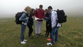 Grupo de turistas novos perdidos que caminham procurando a névoa da calha do sentido que lê o mapa em uma parte superior da monta vídeos de arquivo