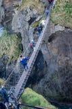 Grupo de turistas que cruzam a ponte de corda famosa na costa norte de do norte imagem de stock