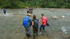 Grupo de turistas que cruzan el río de Mashpi en el área del bosque de la nube en Ecuador Fotos de archivo