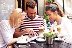 Grupo de turistas que olham o mapa em um café imagens de stock royalty free