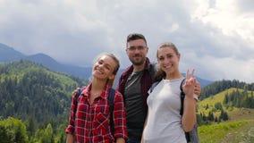 Grupo de turistas que presentan en cámara en montañas en montañas metrajes