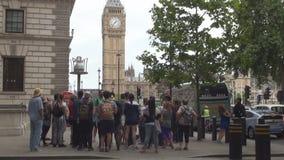 Grupo de turistas que visitan las calles de Londres y a Ben Clock grande en fondo