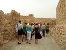 Grupo de turistas que visitan a rey Herod Palace, fortaleza de Masada, desierto de Judaean, Israel foto de archivo