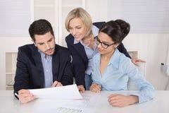 Grupo de un equipo profesional del negocio que se sienta en el talki de la tabla Imagenes de archivo