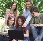 Grupo de universidad/de estudiantes universitarios con el ordenador portátil Fotografía de archivo libre de regalías