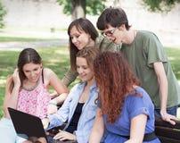 Grupo de universidad/de estudiantes universitarios con el ordenador portátil Imágenes de archivo libres de regalías