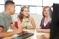 Grupo de Unposed de empresários de negócio criativos em um escritório aberto do conceito que conceitua junto em uma tabuleta digi Imagem de Stock Royalty Free