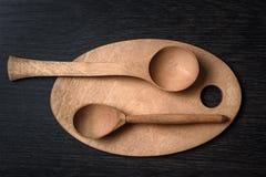 grupo de utensílios de madeira das colheres e das placas de corte no fundo escuro Imagens de Stock Royalty Free