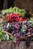 Grupo de uvas coloridas na cesta de vime na prateleira de madeira Imagens de Stock Royalty Free