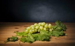 Grupo de uvas verdes na tabela de madeira marrom Imagem de Stock