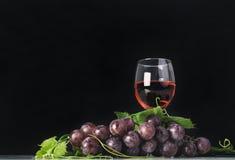 Grupo de uvas vermelhas com folhas e vidro de vinho tinto Fotos de Stock