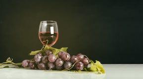 Grupo de uvas vermelhas com folhas e vidro de vinho tinto Imagens de Stock