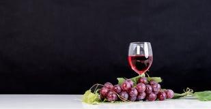 Grupo de uvas vermelhas com folhas e vidro de vinho tinto Imagens de Stock Royalty Free