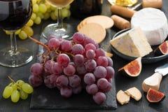 Grupo de uvas vermelhas, de queijos sortidos e de aperitivos Fotos de Stock