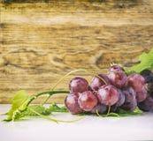 Grupo de uvas vermelhas e folhas e teste padrão de madeira Foto de Stock Royalty Free