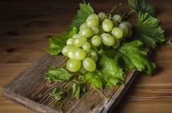 Grupo de uvas vermelhas na tabela de madeira Imagens de Stock