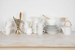 Grupo de vários dishware e cutelaria brancos na tabela de madeira fotografia de stock royalty free