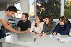 Grupo de varón joven y de estudiantes universitarios de sexo femenino del adolescente en la escuela que se sienta en sala de clas Foto de archivo libre de regalías