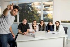 Grupo de varón joven y de estudiantes universitarios de sexo femenino del adolescente en la escuela que se sienta en sala de clas Foto de archivo
