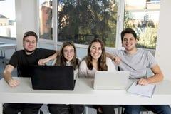 Grupo de varón joven y de estudiantes universitarios de sexo femenino del adolescente en la escuela que se sienta en sala de clas Fotografía de archivo