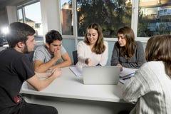 Grupo de varón joven y de estudiantes universitarios de sexo femenino del adolescente en la escuela que se sienta en sala de clas Imagen de archivo libre de regalías