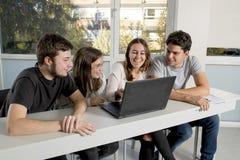 Grupo de varón joven y de estudiantes universitarios de sexo femenino del adolescente en la escuela que se sienta en sala de clas Fotografía de archivo libre de regalías