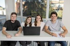 Grupo de varón joven y de estudiantes universitarios de sexo femenino del adolescente en la escuela que se sienta en sala de clas Imagen de archivo