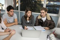 Grupo de varón joven y de estudiantes universitarios de sexo femenino del adolescente en la escuela que se sienta en sala de clas Fotos de archivo libres de regalías