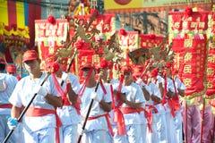 Grupo de varón que lleva a cabo etiquetas rojas con lengua china en desfile Imagen de archivo libre de regalías