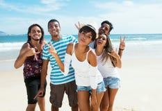 Grupo de varón y de adultos jovenes femeninos que bailan en la playa Imagen de archivo