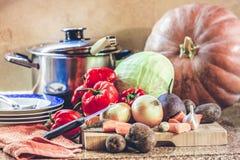 Grupo de vegetais e de pratos na mesa de cozinha Imagens de Stock