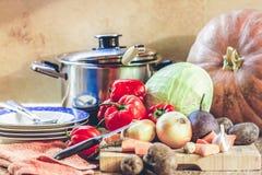 Grupo de vegetais e de pratos na mesa de cozinha Foto de Stock Royalty Free