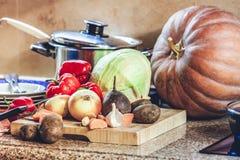 Grupo de vegetais e de pratos na mesa de cozinha Imagem de Stock