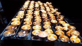 Grupo de velas ardiendo del fuego brillante en un tenedor del metal fotografía de archivo libre de regalías