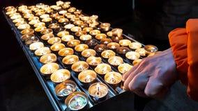 Grupo de velas ardiendo del fuego brillante en un tenedor del metal imagen de archivo
