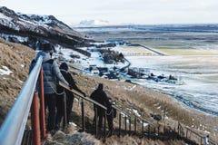 Grupo de viajeros que caminan abajo de las escaleras en invierno en la cascada de Skogafoss que hace turismo en Islandia Imagenes de archivo