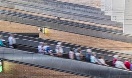 Grupo de viajeros que van abajo para las escaleras móviles en la estación de tren, Sevilla Foto de archivo libre de regalías