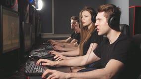 Grupo de videojugadores masculinos y femeninos adultos que se sientan en fila detrás de los monitores, juego en centro del juego  almacen de metraje de vídeo