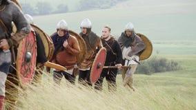 Grupo de Viking con los escudos que camina adelante en el prado