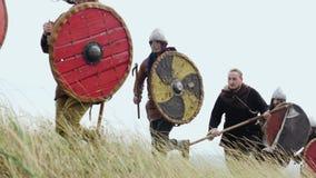 Grupo de Viking con los escudos que corren adelante en el prado y la espada de los aumentos metrajes
