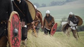 Grupo de Viking medieval con los escudos que camina adelante en el prado